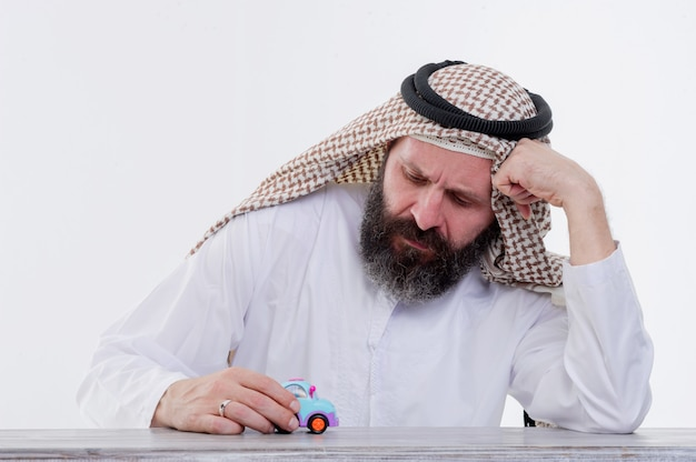 Uomo arabo che si siede al tavolo che tiene un'automobile del giocattolo.