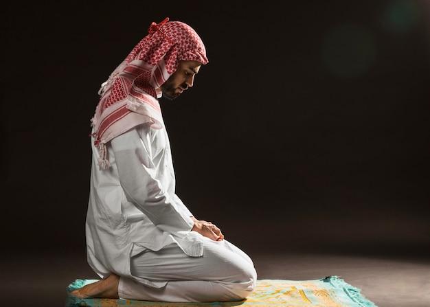Uomo arabo con kandora che si siede sulla vista laterale del tappeto di preghiera