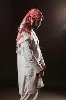 Uomo arabo con kandora in piedi e pregando