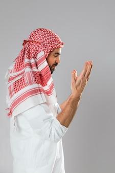 Uomo arabo con kandora in piedi lateralmente