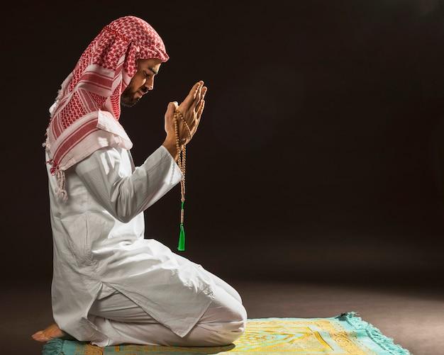 Uomo arabo con kandora seduto sul tappeto di preghiera
