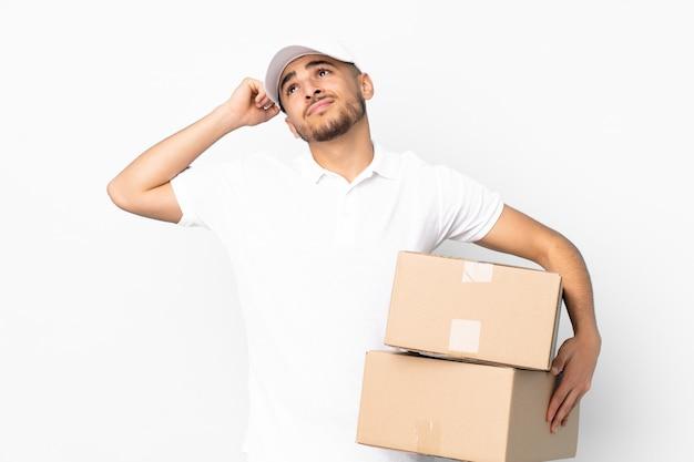 Uomo arabo di consegna sulla parete blu con dubbi e con espressione del viso confuso