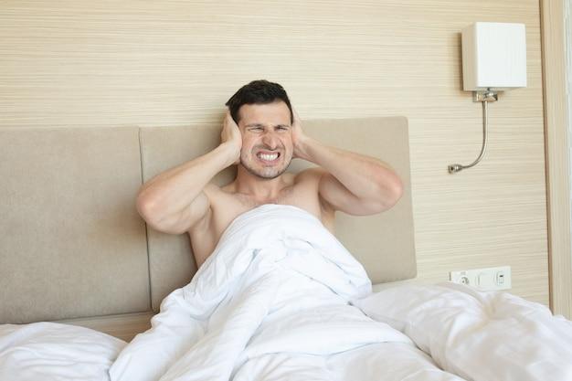 Uomo arrabbiato a letto svegliato da un rumore.