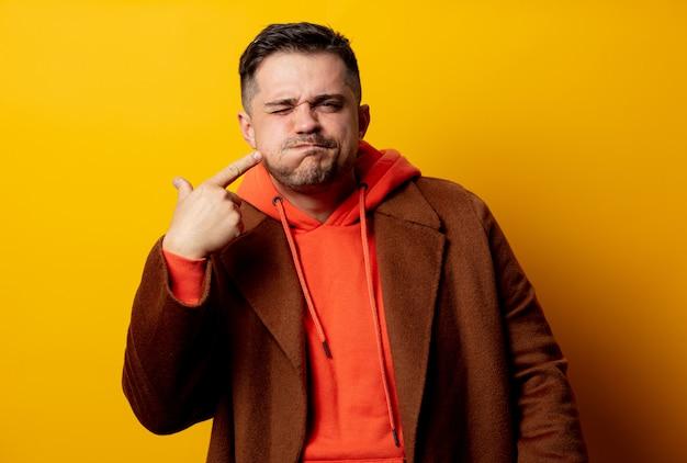 Uomo arrabbiato in cappotto con mal di denti sulla parete gialla