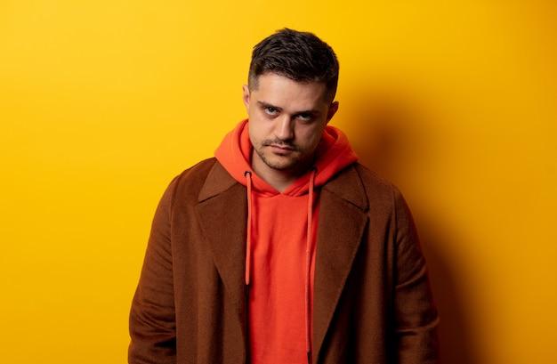 Uomo arrabbiato in cappotto sulla parete gialla
