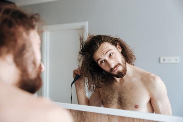 Uomo asciugare i capelli con asciugacapelli a casa