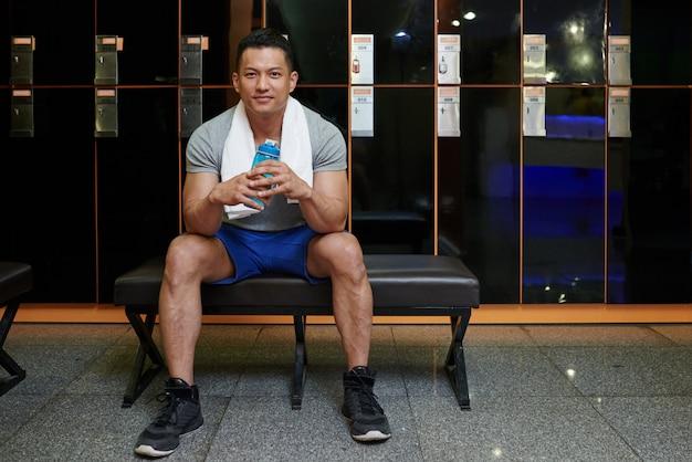 Uomo asiatico adatto che si siede sul banco nello spogliatoio in palestra e che tiene bottiglia di acqua