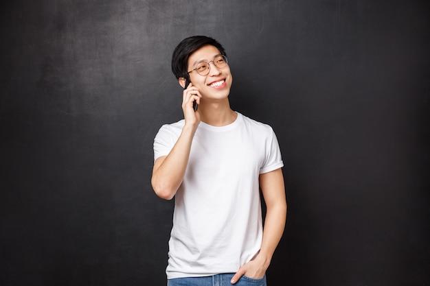 Uomo asiatico allegro spensierato che parla sul telefono con l'atteggiamento amichevole