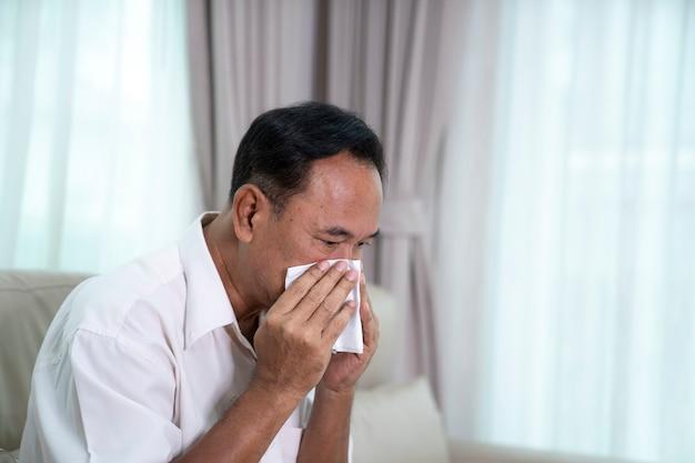 Uomo asiatico anziano malato con le pillole che questa immagine può usare per il concetto di covis19, del virus e del faver