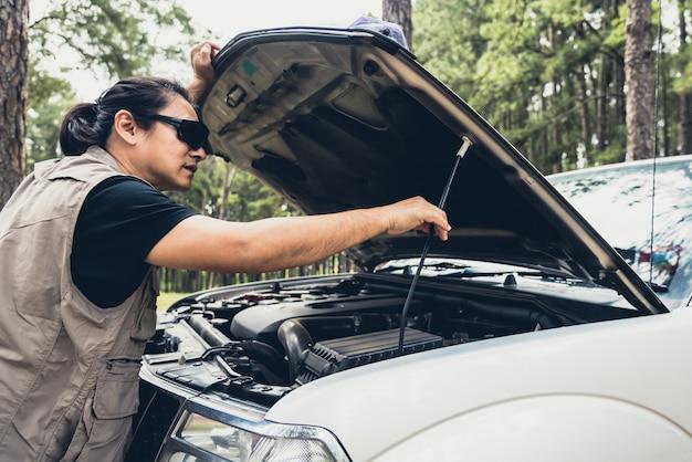 Uomo asiatico aprendo il cofano del suo camioncino per verificare le condizioni di avaria del motore