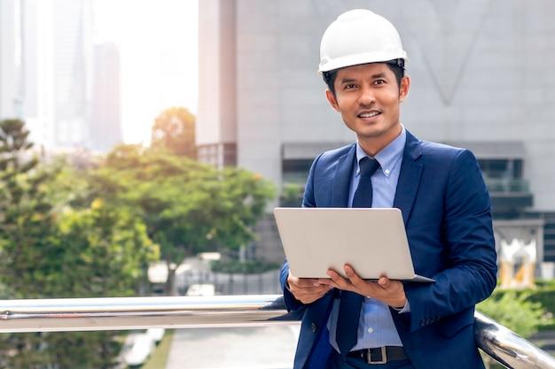 Uomo asiatico astuto del responsabile dell'ingegnere di affari che sta e che lavora con il computer portatile alla città all'aperto.