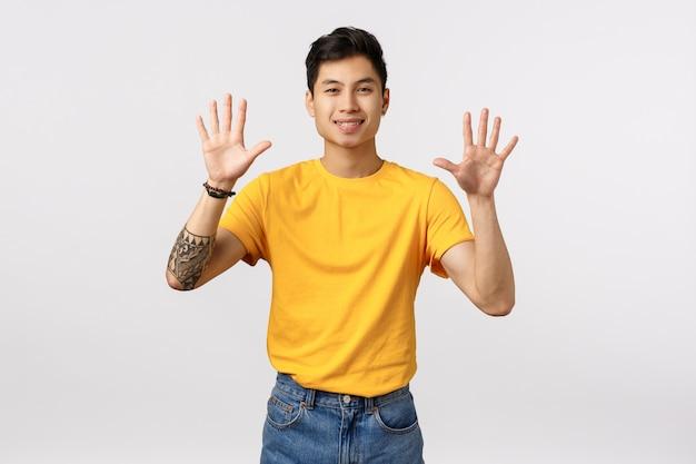 Uomo asiatico attraente allegro e dall'aspetto amichevole in maglietta gialla, con tatuaggi, che mostra dieci dita, alzando le braccia, ordina una dozzina, sorridendo con gioia, in piedi muro bianco ottimista