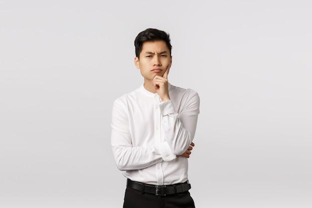 Uomo asiatico attraente sospettoso e scettico, riflessivo in camicia, pantaloni, accigliato sguardo macchina fotografica con incredulità e faccia seria, toccare il mento, pensare, avere ipotesi, in piedi