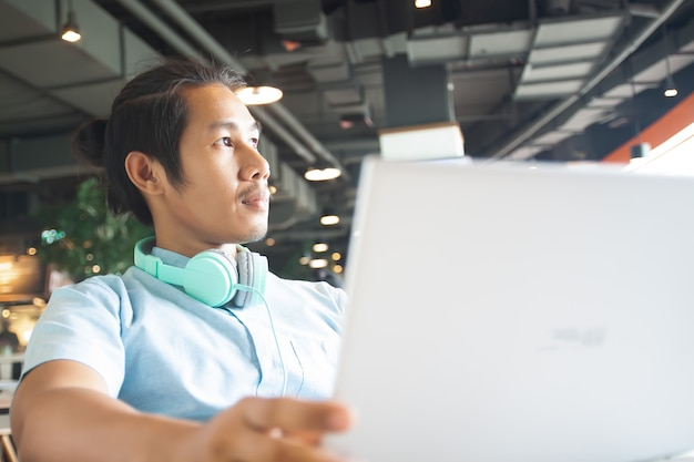 Uomo asiatico bello che per mezzo del computer portatile. concetto di avvio aziendale