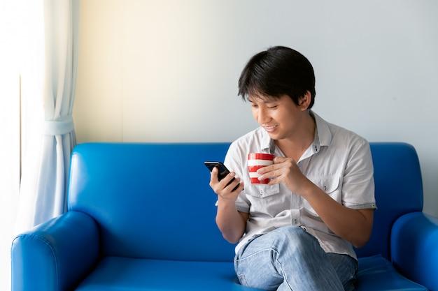 Uomo asiatico bello che utilizza telefono cellulare bevendo un certo caffè e sedendosi sul sofà blu alla mattina