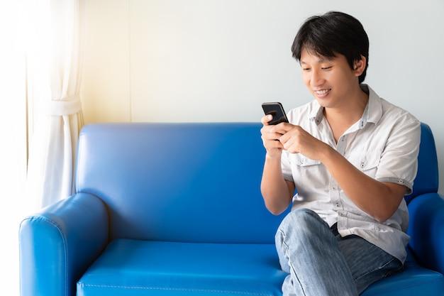 Uomo asiatico bello che utilizza telefono cellulare mentre sedendosi sul sofà blu alla mattina