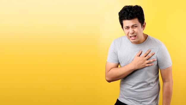 Uomo asiatico bello con dolore del cuore, sulla parete gialla.