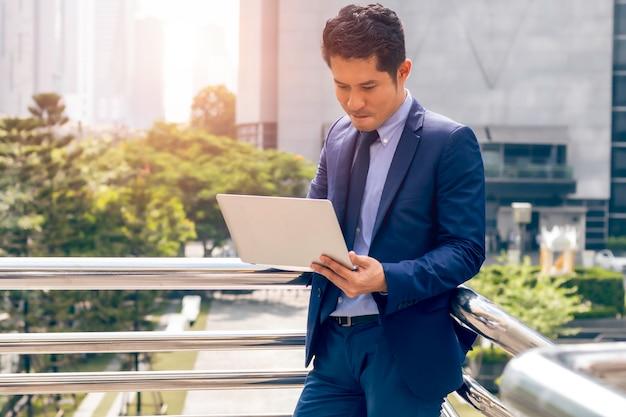 Uomo asiatico bello del direttore aziendale che sta e che lavora con il computer portatile alla città all'aperto.