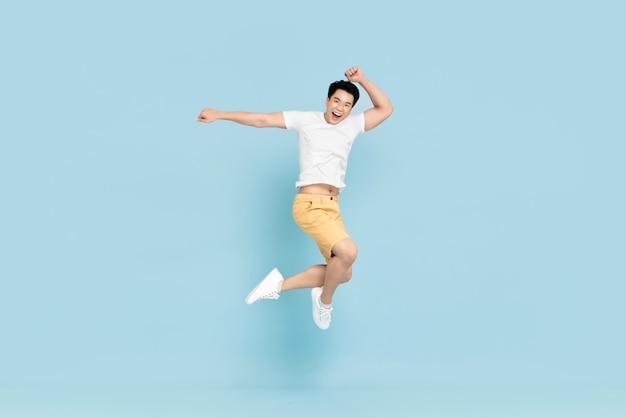 Uomo asiatico bello felice che sorride e che salta