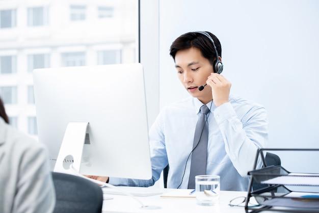 Uomo asiatico bello messo a fuoco che lavora nell'ufficio della call center come operatore di telemarketing