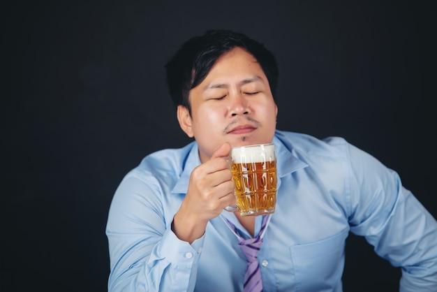 Uomo asiatico che beve un boccale di birra