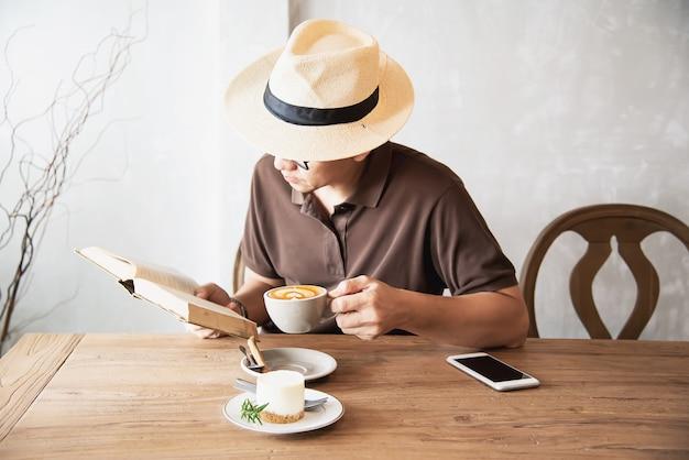 Uomo asiatico che beve un caffè e che legge un libro