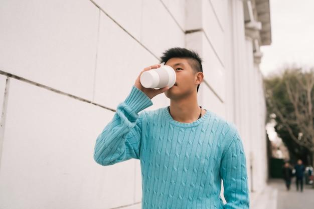 Uomo asiatico che beve una tazza di caffè.