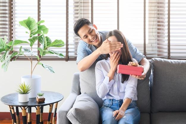 Uomo asiatico che dà un regalo presente per sorprendere la sua ragazza a casa