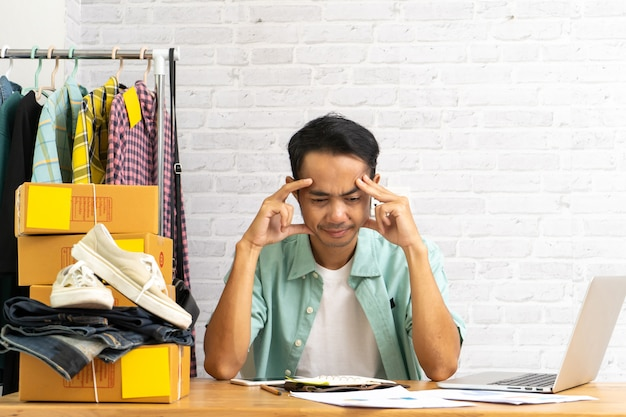 Uomo asiatico che è frustrato che lavora computer portatile funzionante, vendente in linea