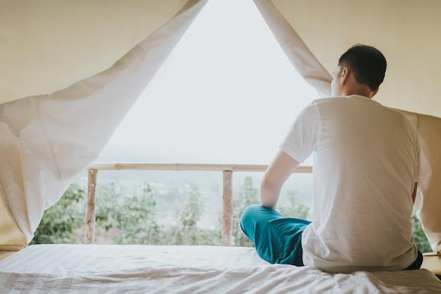 Uomo asiatico che esamina il mountain view dalla tenda nel tempo di tramonto