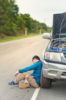 Uomo asiatico che ha problemi con la sua auto rotta