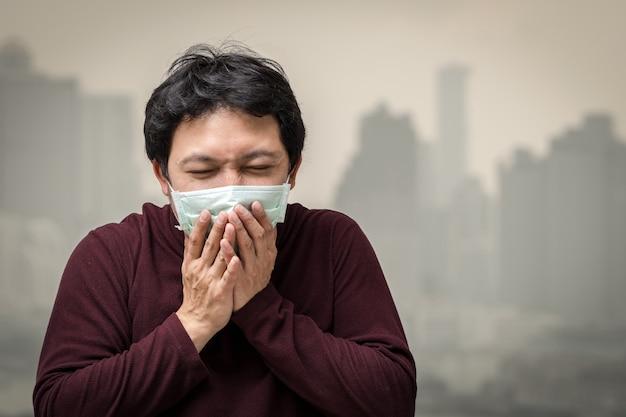 Uomo asiatico che indossa la maschera contro l'inquinamento atmosferico con la tosse