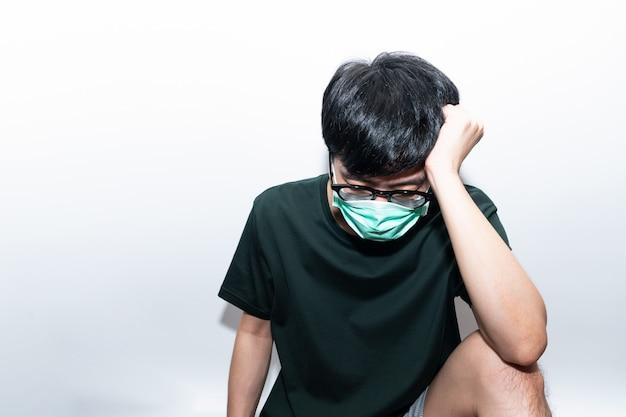 Uomo asiatico che indossa maschera protettiva depresso e stressato
