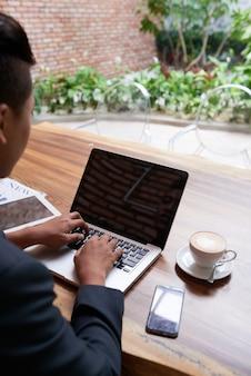 Uomo asiatico che lavora al computer portatile nel caffè all'aperto del giardino