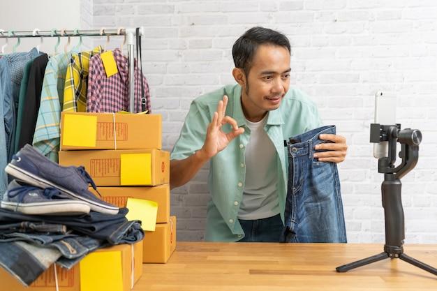 Uomo asiatico che mostra bene e che per mezzo del telefono cellulare astuto che prende vendita dal vivo