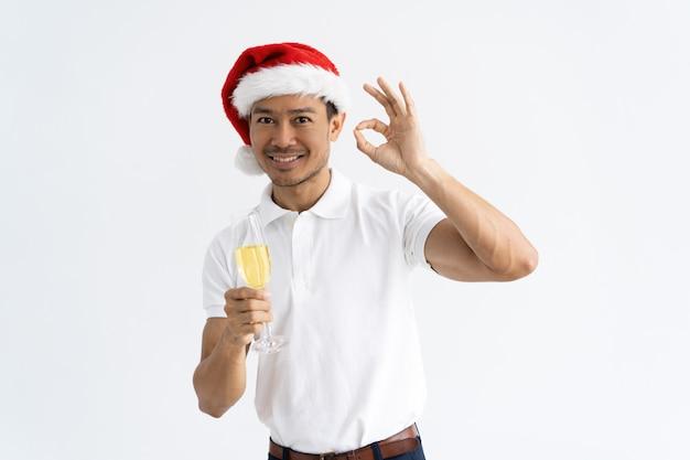Uomo asiatico che mostra segno giusto e che tiene calice con champagne