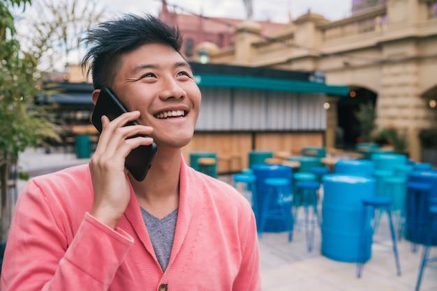 Uomo asiatico che parla al telefono all'aperto.