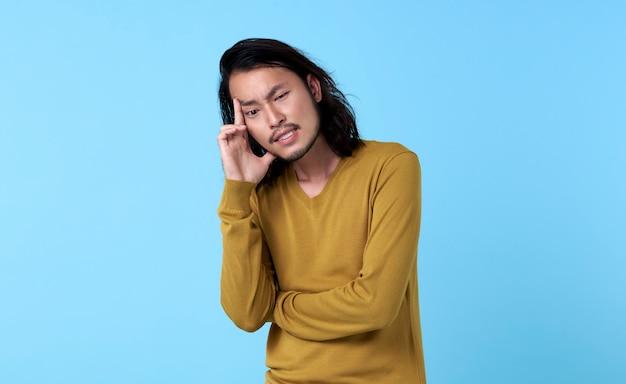 Uomo asiatico che pensa duro per qualcosa nella reazione di espressioni facciali di emozione isolata