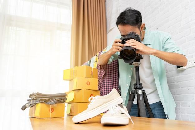Uomo asiatico che prende foto alle scarpe con la macchina fotografica digitale per la posta alla vendita online