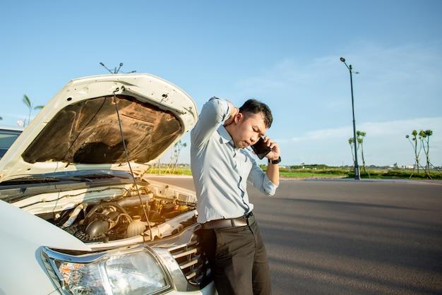 Uomo asiatico che richiede l'aiuto di un'automobile rotta sulla strada
