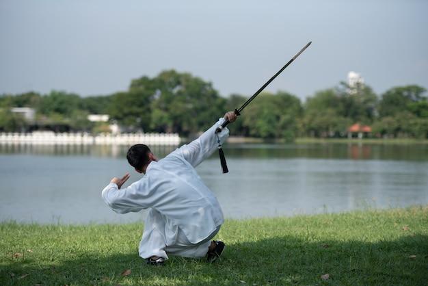 Uomo asiatico che risolve con la spada di tai chi di mattina al parco, arti marziali cinesi, cura sana per il concetto di vita.