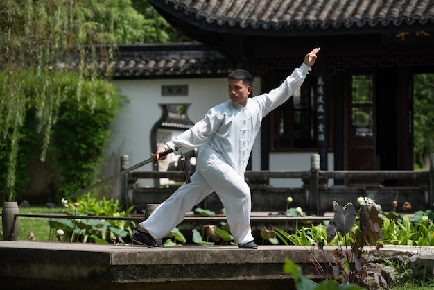 Uomo asiatico che risolve con la spada di tai chi di mattina al parco, arti marziali cinesi
