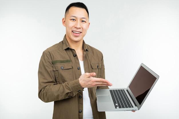 Uomo asiatico che scrive su una tastiera del computer portatile su uno studio bianco