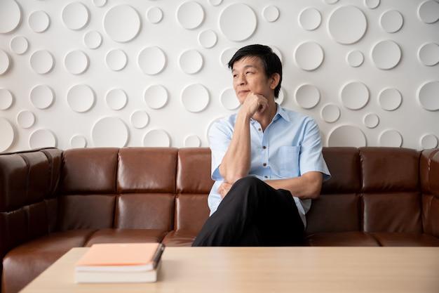 Uomo asiatico che si distende nel salone