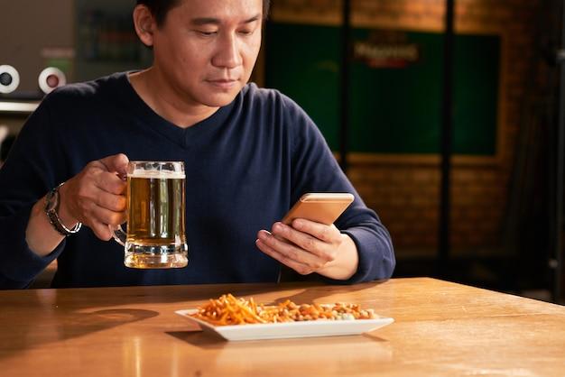 Uomo asiatico che si siede nel pub con birra e spuntini e che per mezzo dello smartphone