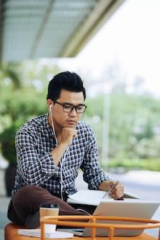 Uomo asiatico che si siede sul banco all'aperto con il computer portatile e che ascolta il webinar online