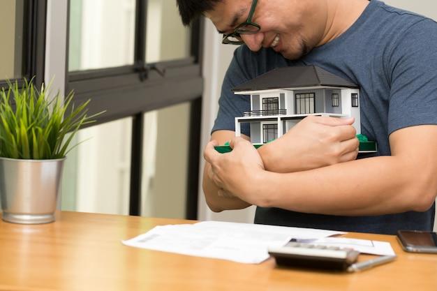 Uomo asiatico che sorride e abbraccia una casa dei sogni e calcola di comprare una casa sognando il suo futuro