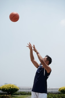 Uomo asiatico che sta all'aperto allo stadio e che getta baseball su in aria