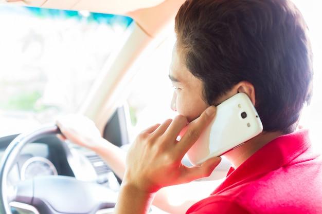Uomo asiatico che telefona mentre guida l'automobile