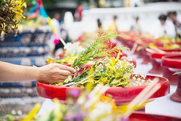 Uomo asiatico che tiene i fiori gialli freschi per cerimonia buddista tradizionale locale di partecipazione, la gente con la relazione di religione